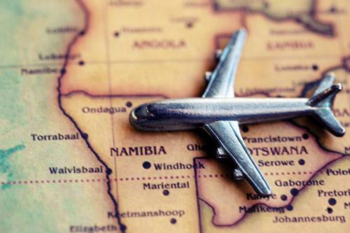 Silbernes Flugzeugmodell auf einer Landkarte. Der Name Namibia ist gut zu sehen