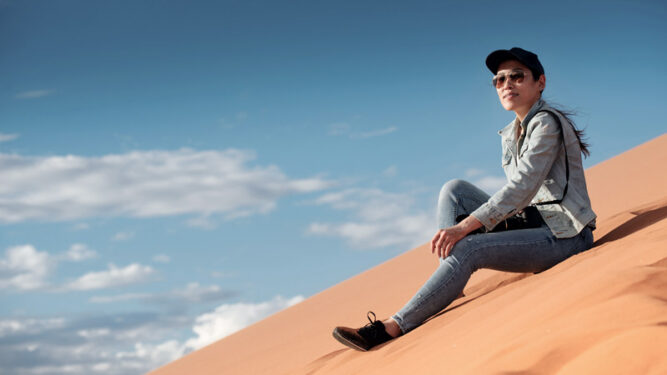Frau mit angewinkeltem Bein auf einer großen Sanddüne. Leicht bewölkter Himmel