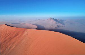 Blick auf rötliche große Sanddünen, blauer Himmel