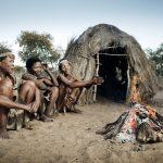 Drei afrikanische Stammesleute vor einer Strohhütte