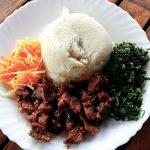 Ein Speisenteller mit Maisbrei, Gemüse, Fleisch und Karotten