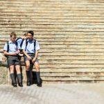 Drei Schuljungen mit Schuluniform vor einer Treppe