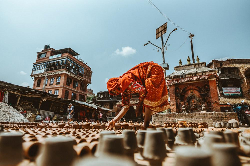 frau in roter nepalesischer kleidung beugt sich zu tontöpfen runter