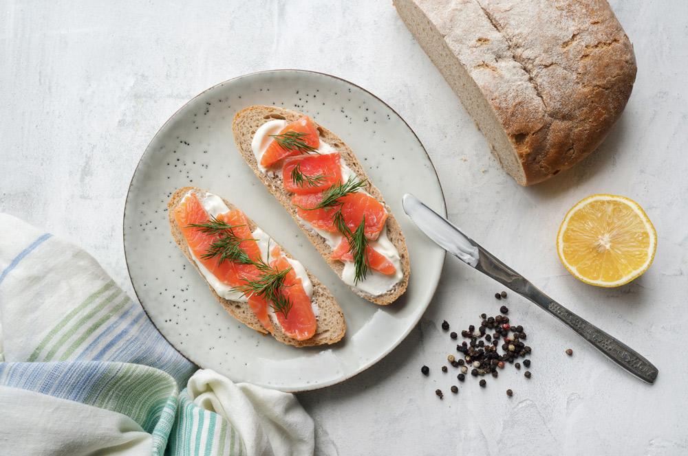Blick von oben auf Teller mit zwei Scheiben Brot mit Lachst und Dill drauf.