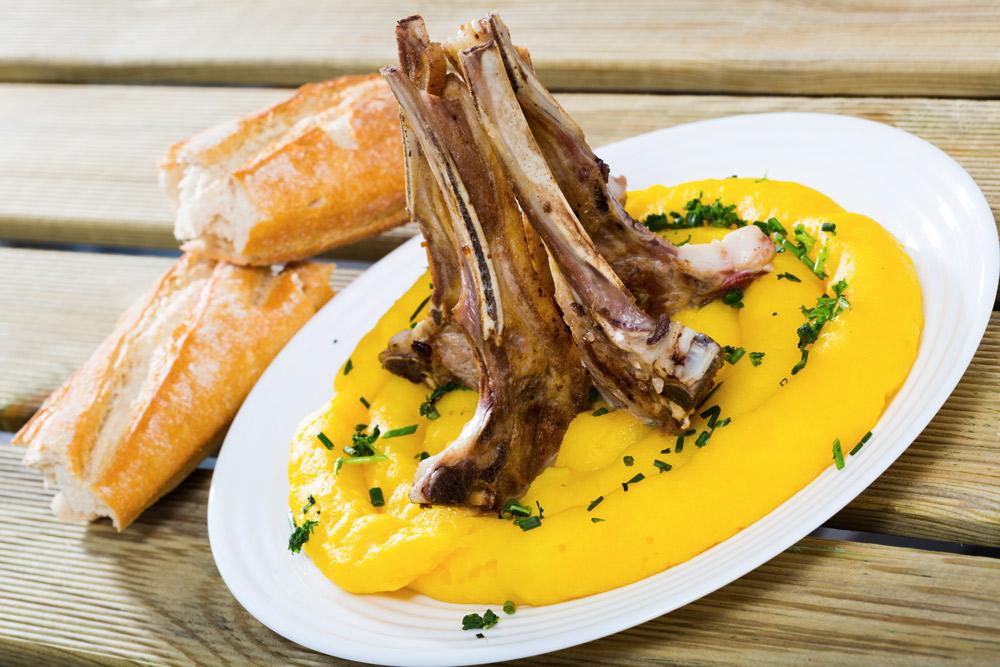 knochen mit fleisch auf teller mit gelbem püree, daneben zwei stücke baguette