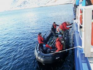 Mehrere Personen steigen in ein schwarzes Schlauchboot ein