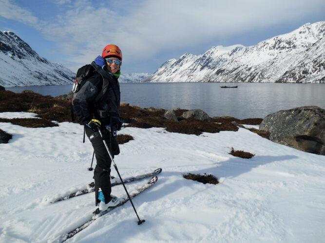 Skitourengeher lächelt in die Kamera, steht an einer verschneiten Bucht vor dunkelblauem Meer