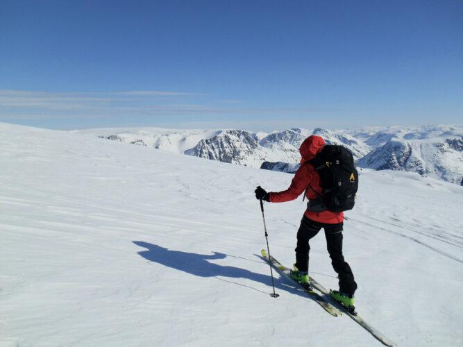 Ein Skitourengeher mit roter Jacke von hinten, weiße Landschaft und verschneite Berge im Hintergrund, klarer Himmel