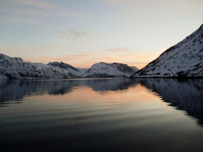 Himmel kurz nach Sonnenuntergang an Meeresbucht, schwarzes Wasser und verschneite Berge