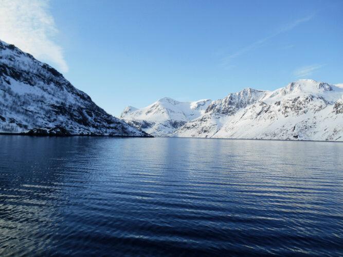 Dunkelblaues Wasser umgeben von verschneiten Bergen, klarer Himmel