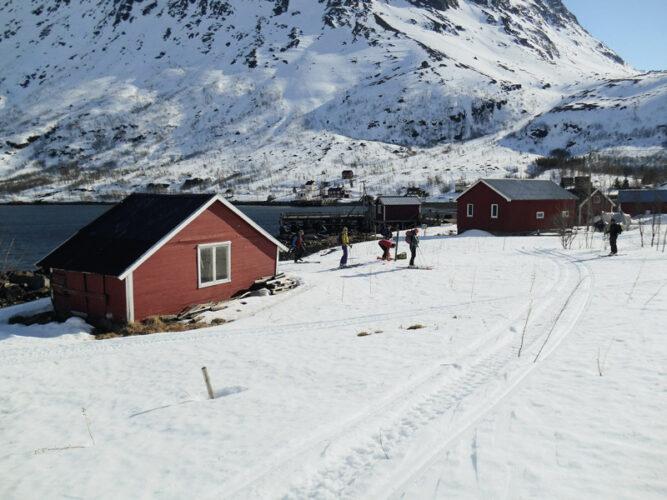 Rote kleine Häuser in verschneiter Landschaft, Wasser im Hintergrund