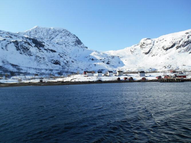 Dunkles Wasser, im Hintergrund verschneite Berge, Häuser in der Bucht