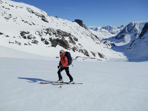 Skitourengeher auf glatter, verschneiter Strecke, klarerHimmel