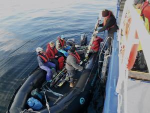 Mehrere Personen geben Rucksäcke und Skier in ein schwarzes Schlauchboot