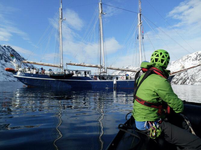 Person mit grüner Jacke auf einem Boot, fährt in Richtung größerem Boot, wenige Wolken am Himmel