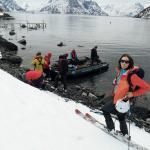 Einige Personen bei und auf einem Schlauchboot in der Bucht, eine Person im Vordergrund schaut in die Kamera