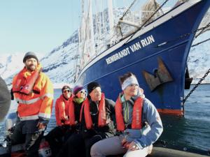 Einige Personen mit Rettungswesten blicken nach rechts und sitzen auf einem Schlauchboot, im Hintergrund ein großes blaues Boot