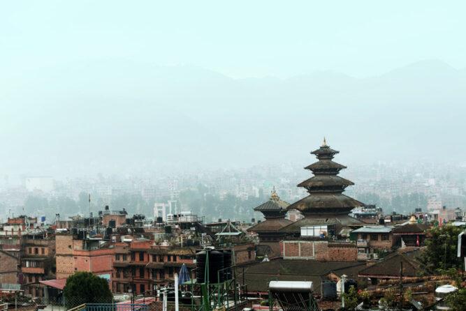 Nebelig kühles Wetter, viele Häuser und ein herausragender Turm rechts im Bild