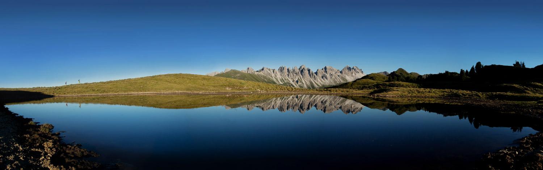 see, in dem sich berge am horizont spiegeln