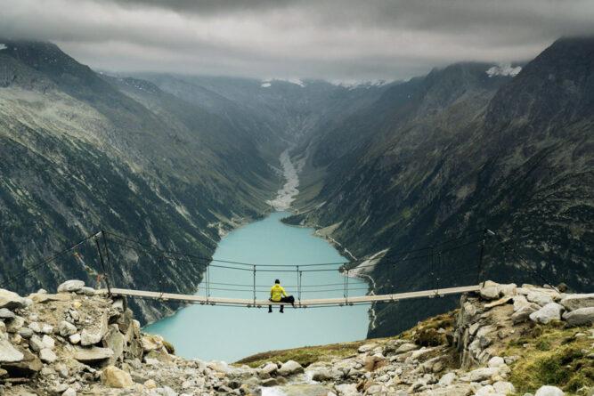 wanderer auf hängebrücke mit blick über hellblauen see, dunkle bergwände links und rechts