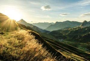 Sonnenaufgang in geschichteter Bergsilhoutten an einem Sommertag.