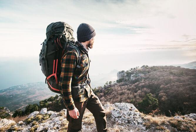 Junger Mann mit vollgepacktem Wanderrucksack in den Bergen.