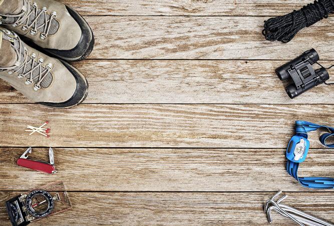 Wanderutensilien liegt auf hellem Holzboden