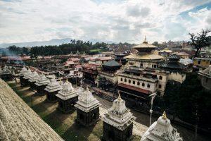 Tempelkomplex mit einem Fluss in der Mitte. Im Hintergrund steigt Rauch auf.