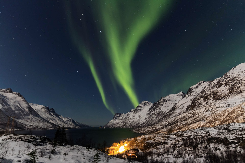 verschneite Berge und Meer unter nächtlichem Himmel und grünlichem Licht