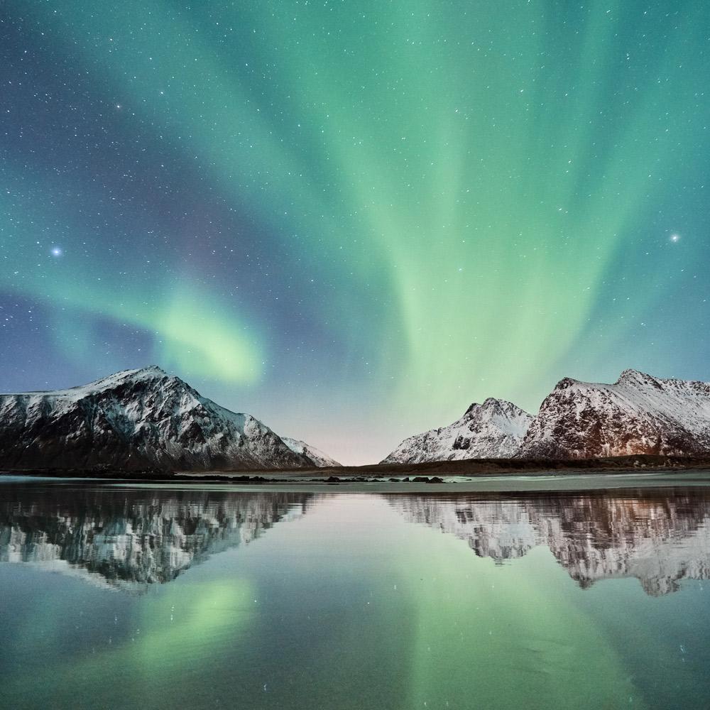 See und Berge und nächtlicher Himmel mit grünem Licht