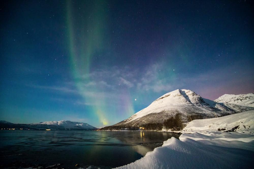 Nachthimmel blau mit grünem und violettem Schimmer über mit Schnee bedeckten Bergen am Meer