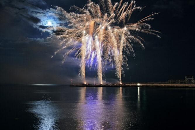 Goldenes Sprüh-Feuerwek auf Nachthimmel. Mond schimmert Blau hinter dunklen Wolken