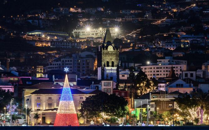 Bunt leuchtende Stadt. Ein Weihnachtsbaum aus roten, weißen und blauen Lichtern. In der Mitte ein Kirchturm.