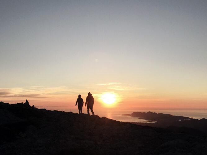 Sonnenuntergang auf einem Berg, roter Himmel und schwarze Umrisse, Silhouetten zweier Wanderer