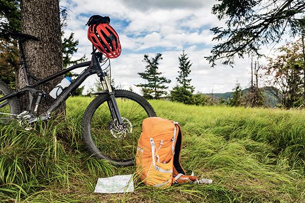 Fahrrad mit rotem Helm und orangenem Rucksack an einem Baum