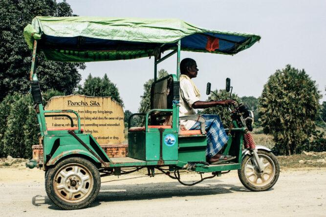Grünes, offenes Fahrzeug mit 3 Rädern. Eine Person am Steuer