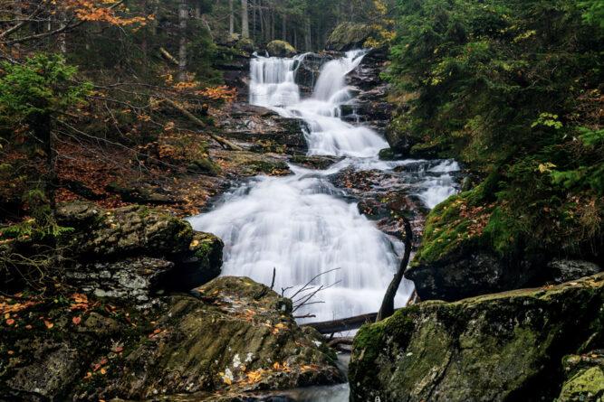 Kristallklare kleine Wasserfälle durch den herbstlichen Wald, Deutschland