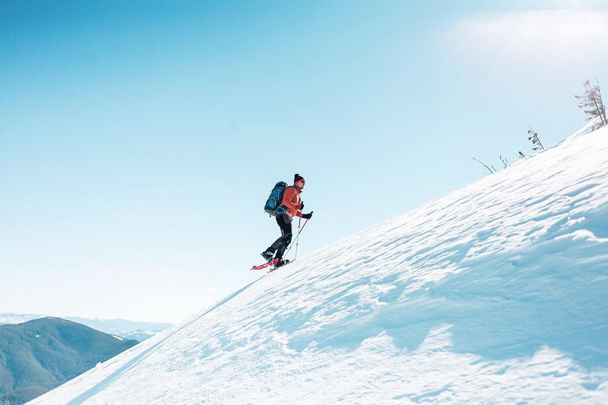 Mann auf Schneeschuhen erklimmt mit Schnee bedeckten Berg