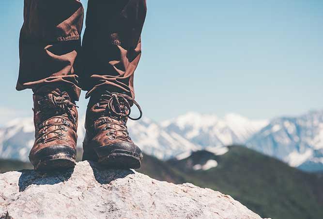 Wanderer auf Stein mit Schuhen