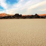 Der trockene, Rissige Boden des Death Valley Nationalpark mit Ausblick auf die Berge. © Shutterstock