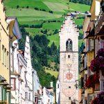 Ein schmaler Kirchturm mit bunten Malereien. Im Hintergrund grüne Wiesen