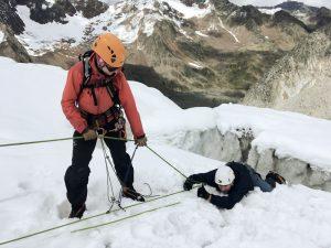 Mann mit roter alpiner Ausrüstung zieht Mann aus Gletscherspalte.