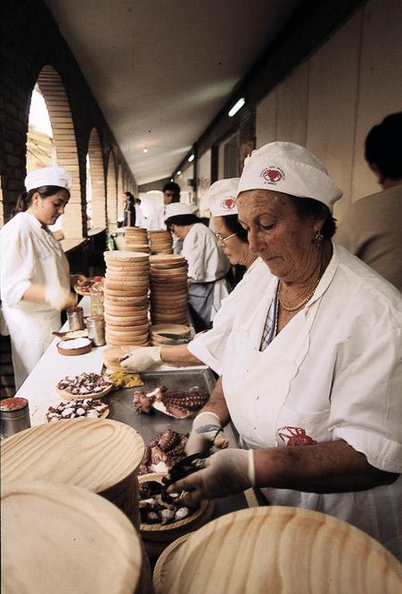 Eine Gruppe von Frauen in weißer Kleidung, welche frische Speisen aus Meeresfrüchten zubereiten