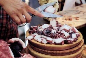 Nahaufnahme des Polbo à feira, ein traditionelles Gericht der galicischen Küche aus marinierten, getrocknete Oktopus. Fischer richtet das Gericht auf einem kleiner Holzteller an.