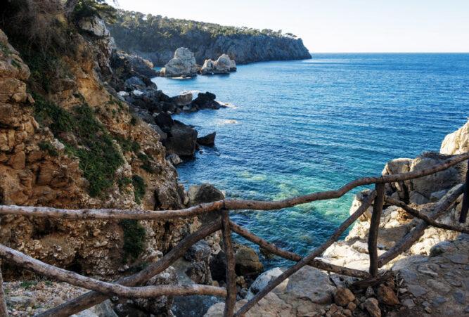 Blick von Küste auf Meer, hölzerner Zaun als Abtrennung