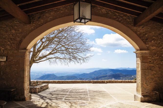 Großer steinerner Torbogen mit Ausblick auf Berge in der Ferne, blauer Himmel