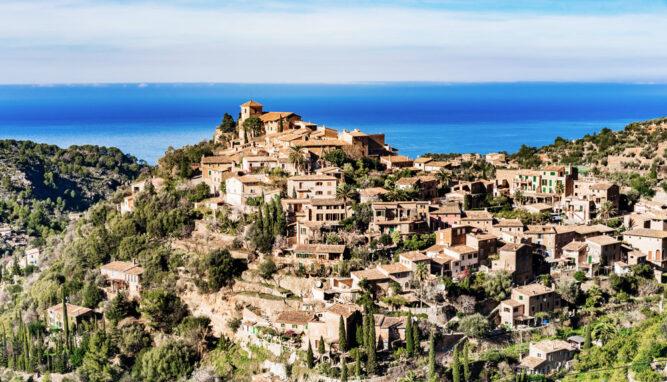 Sandfarbene Häuser auf einem Hügel in Deiá