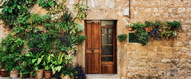 Eingangstür rustikal auf Mallorca mit Blumen.