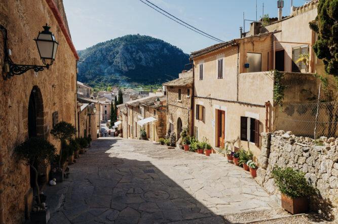 Straße mit großen Pflastersteinen, sandfarbige Gebäude drumrum, ein Hügel im Hintergrund