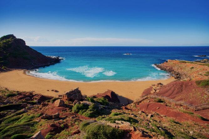 Bucht mit rötlichem Sand und hellblauem Wasser. Rote Hügel